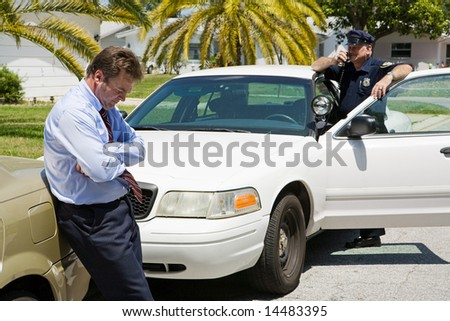 Embarrassed looking businessman pulled over by the police.  Focus is on the businessman. - stock photo