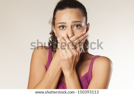 embarrassed young brunette covering her mouth with both hands - stock photo