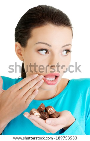Embarrassment beautiful woman with hand full of chocolates  - stock photo