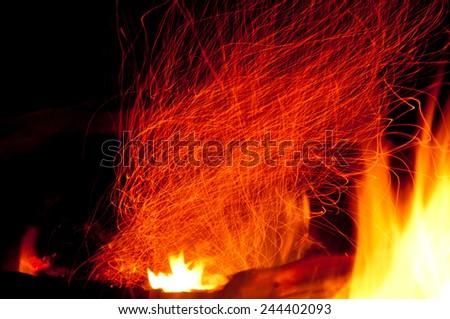 Embers in a fire glow and swirl upward. - stock photo