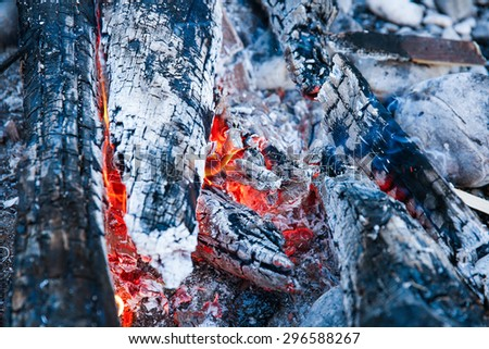 Embers of a self-made campfire, lit for cooking, roasting and water purification. Safety and survival, outdoor activity concept.  - stock photo