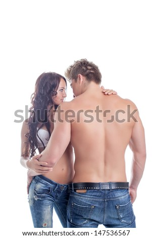 Embrace of semi-nude couples posing in jeans - stock photo