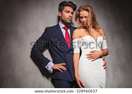 embraced elegant fashion couple standing in studio with hands on hips , man looks away to a side and woman looks down, in studio - stock photo
