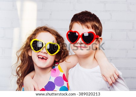 Embracing boy and girl with sunglasses heart shape.  Happy toothless smiling friend. Toning instagram filter. - stock photo