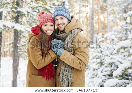 Embracing couple looking at camera with smiles in winter park - stock photo