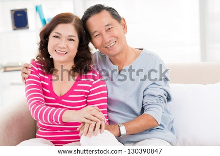 Embracing couple sitting on the sofa indoors - stock photo