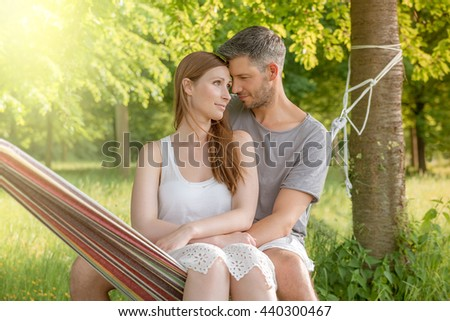 embracing couple together in hammock - stock photo