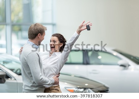 Embracing couple with car keys - stock photo