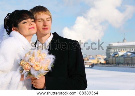 embracing smiling groom and bride with closed eyes holding bouquet of roses at winter outdoors, couple standing on bridge - stock photo