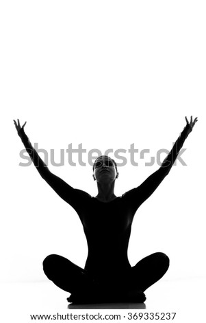 Embracing the world. Silhouette of a yoga woman sitting with her hands raised to the copyspace above isolated on white - stock photo