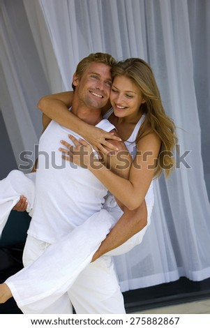 Embracing young blond couple. The young man is carrying the young girl on his back. - stock photo