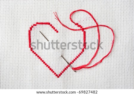 embroidered red heart on white canvas - stock photo