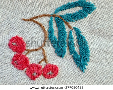 Embroidered tree branch with leaves and red berries on the tablecloth       - stock photo