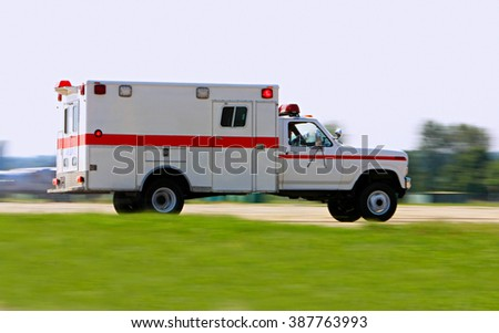 Emergency ambulance driving very fast - stock photo