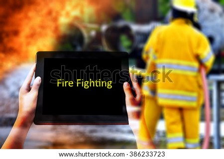 "Emergency Concept. "" FIRE FIGHTING"" words in yellow  on tabled in hands and fireman in action firefighting background. - stock photo"