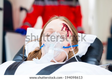Emergency doctor and nurse or ambulance team transporting accident victim on stretcher - stock photo