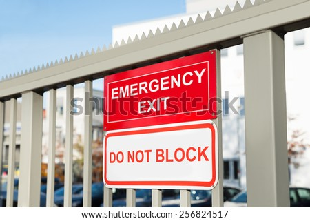 Emergency Exit And Do Not Block Signboard On Gate - stock photo