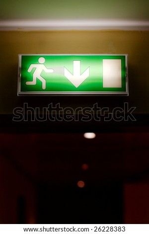 Emergency exit sign glowing in a corridor - stock photo