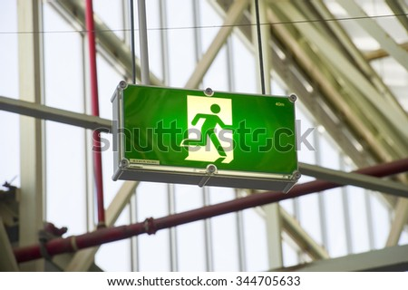Emergency exit sign in industrial building - stock photo