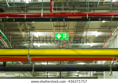 Emergency exit sign, pipe systems, pipeline extinguishing water on industrial building ceiling. - stock photo