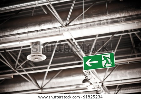 Emergency exit sign under the ceiling of a fair hall - stock photo