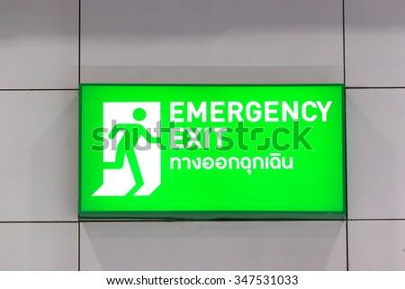 Emergency exit sign with Thai alphabet isolated on white background.  - stock photo