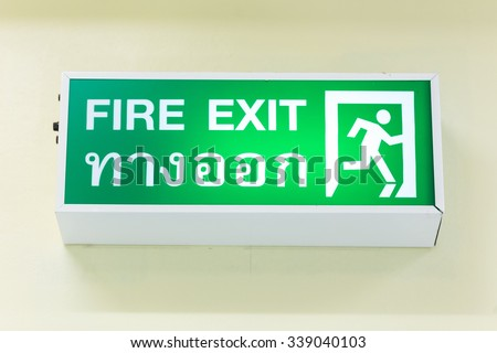 Emergency exit sign with Thai alphabet isolated on white background. - Selective Focus - stock photo
