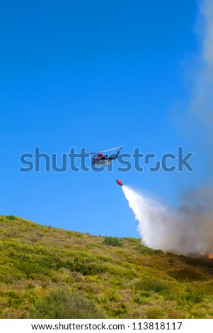 emergency helicopter extinguishes flames of a raging bush fire - stock photo