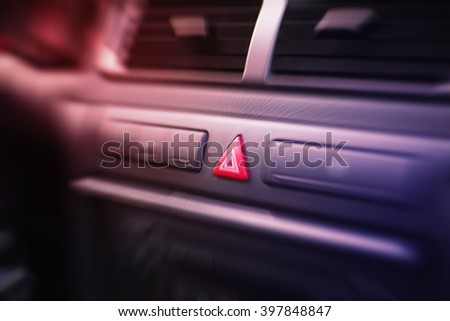 Emergency lights button inside a car. Blurry motion effect. - stock photo