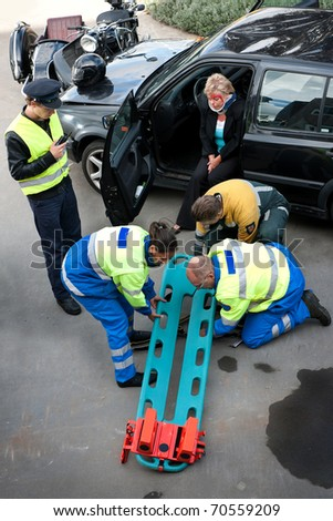 Emergency Medical Services team preparing a stretcher with head block for an injured driver - stock photo