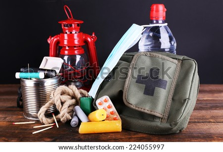 Emergency preparation equipment on wooden table, on dark background - stock photo