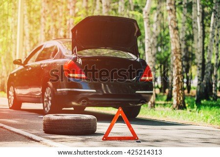 emergency sign and the wheel on the road in the woods - stock photo