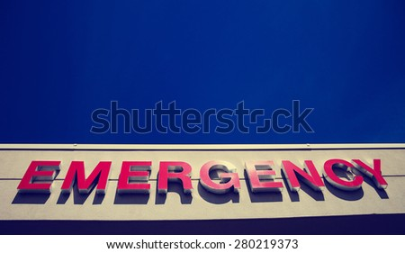 emergency sign with view of open blue sky above the sign on the wall with an instagram retro filter - stock photo