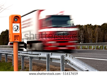 emergency telephone at highway and driving truck - stock photo