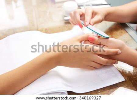 emery polish sandpaper woman nails in Nail Salon - stock photo