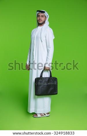 Emirati businessman holding bag - stock photo