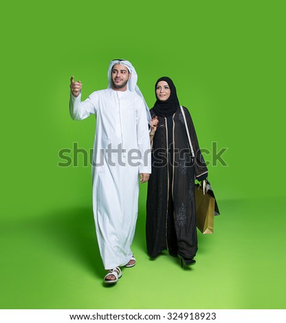 Emirati couple carrying shopping bags - stock photo
