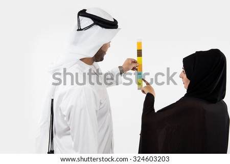 Emirati couple looking at color swatches - stock photo