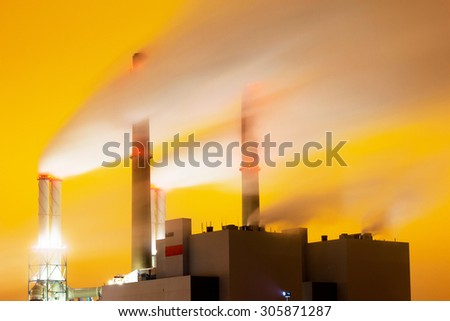 Emission gases of a large power plant at night - Long exposure - (Yellow background is the result of the foggy night conditions combined with industrial lights illuminating the sky)  - stock photo