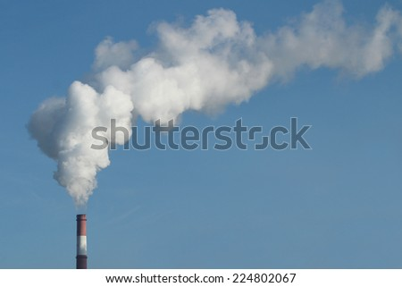 Emission of gases from the chimney at a power plant  - stock photo
