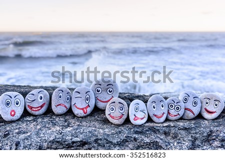 Emoticons on pebbles on the seashore - stock photo