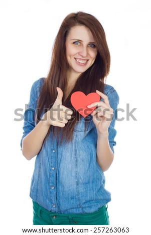 Emotional attractive brunette woman in love. Beautiful young girl in denim blue shirt standing on a white background with a red paper heart in hands. - stock photo