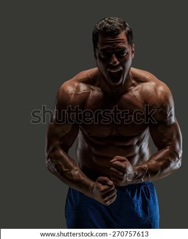 Emotional bodybuilder on grey background - stock photo