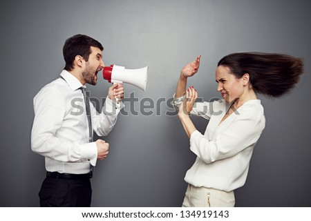 emotional boss reprimanding his subordinate. studio shot over dark background - stock photo