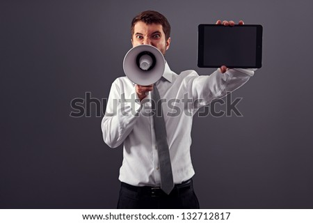 emotional businessman showing the screen of tablet pc and shouting with megaphone against grey background - stock photo