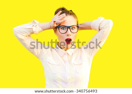 Emotional colorful summer autumn funny pretty girl with fun sunglasses red lips and comic stress excited surprised scream smile laugh. Yellow isolate background. - stock photo