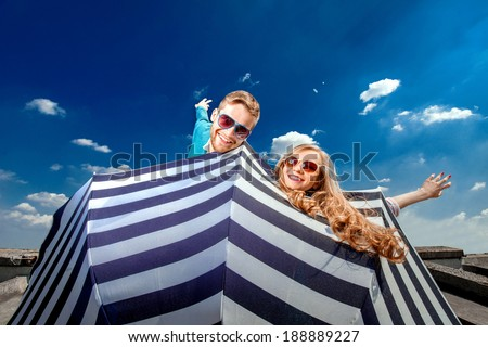 Emotional couple flying with umbrella and having fun on the blue sky background - stock photo
