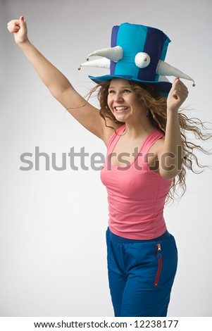 emotional girl in big football fan hat on gray background - stock photo