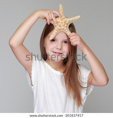 Emotional happy young girl with beautiful long hair holds a beautiful starfish on a gray background on the marine theme - stock photo