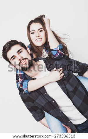 emotional, life style, happiness and people concept: Happy loving couple. Young man piggybacking his girlfriend. Studio shot over white background.Special Fashionable toning photos. - stock photo
